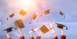 happy graduate in cap and gown with diploma