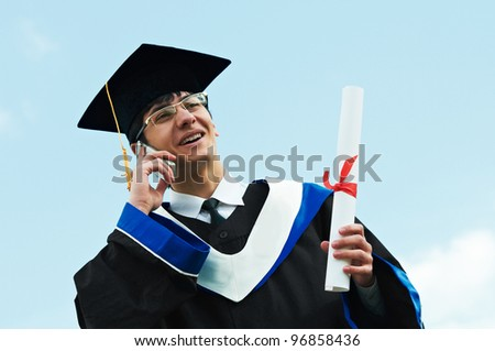 Happy graduate student in gown with diploma speaking on phone over blue sky