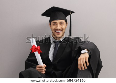 Happy graduate student with a diploma leaning against a gray wall and looking at the camera