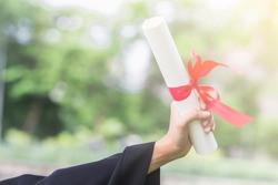 Happy graduate young Asian woman wear black gown and holding a certificated in hand with garden background, Education concept