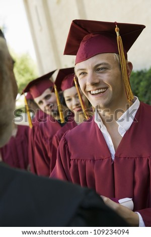 Happy graduates collecting certificate from male dean