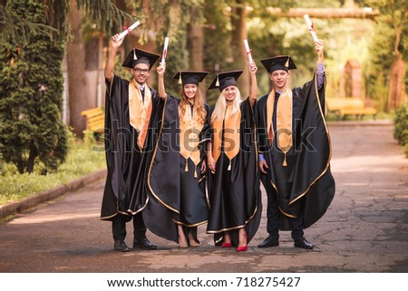Happy graduates in mantles standing in the park and keeping diplomas in hands