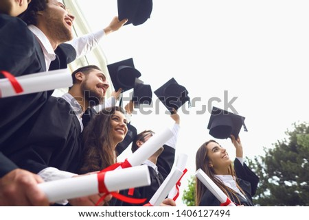 Happy graduates raised their hands with scrolls of diplomas