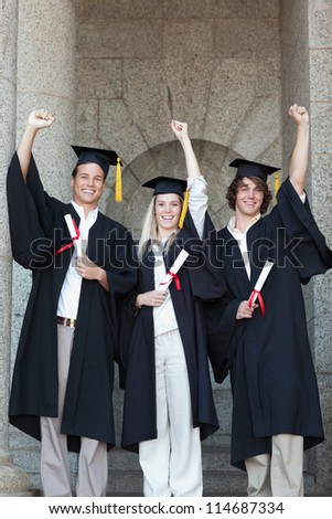 Happy graduates raising arm with university in backgroung - stock photo