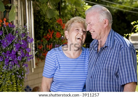 happy grand parents in the summer looking at each other - stock photo