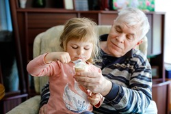 Happy grandfather and cute little toddler granddaughter, adorable child eating together ice cream. Family tasting sweet icecream, baby girl feeding senior man.