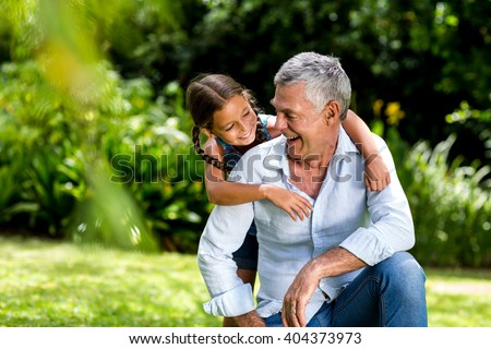 Happy grandfather and grandaughter playing at yard