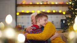 Happy grandfather and grandson embracing sitting on couch celebrating new year. Portrait of cheerful senior man and preteen boy hugging relaxing on sofa on christmas eve