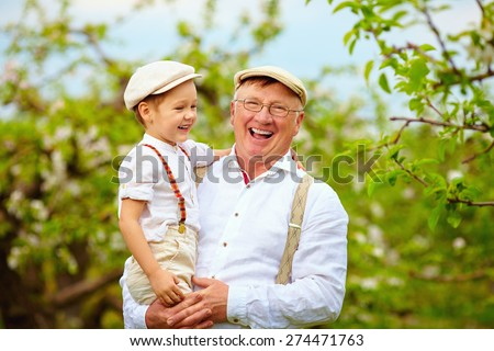 happy grandfather and grandson having fun in spring garden