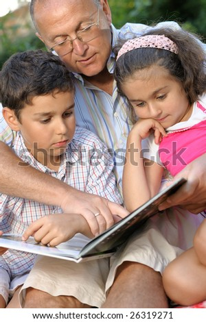 happy grandfather and kids reading book outdoors