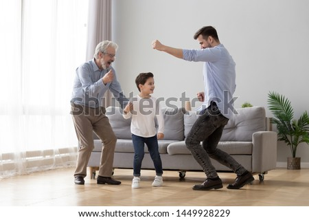 Happy grandfather, father and little son having fun at home, excited granddad, dad and preschool child boy grandchild dancing to favorite music together, family playing in living room, funny activity Stockfoto ©