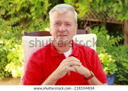 Happy grandfather sitting at garden at home.