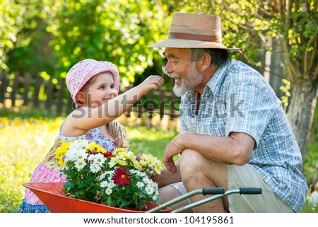 Happy grandfather with his granddaughter in the garden