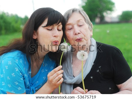 Happy grandmother and grand daughter with dandelions on the meadow