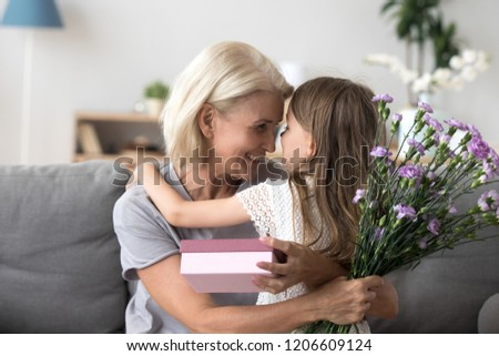 Happy grandmother and granddaughter hug celebrating birthday together, cute little girl congratulate granny presenting gift box and flowers bouquet, grandma thanking grandchild for surprise