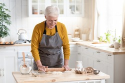 Happy grandmother attractive elderly woman rolling dough for pie or pizza, cheerful senior lady cooking for her family or waiting for guests coming, kitchen interior, copy space