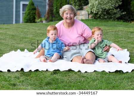 Happy grandmother holding twin boys