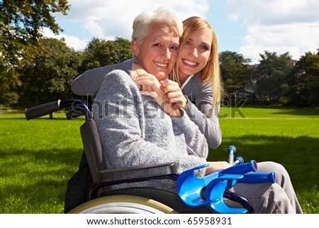 Happy grandmother in wheelchair with her grandchild in a park