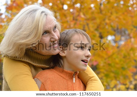 happy grandmother with boy  in the autumn park