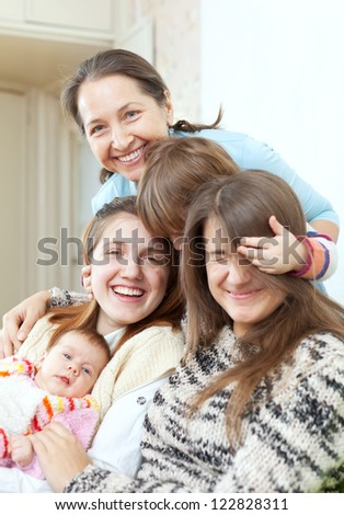 Happy grandmother with her daughters and granddaughters in home