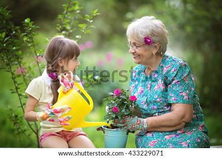 Happy Grandmother with her granddaughter working in the garden