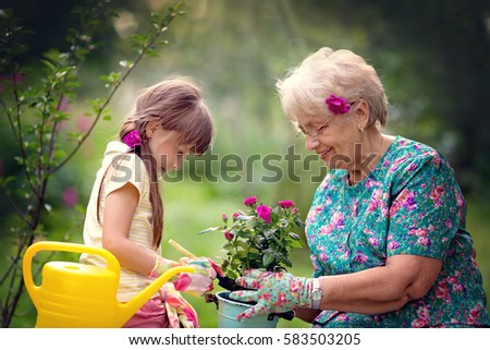 Happy Grandmother with her granddaughter working in the garden.