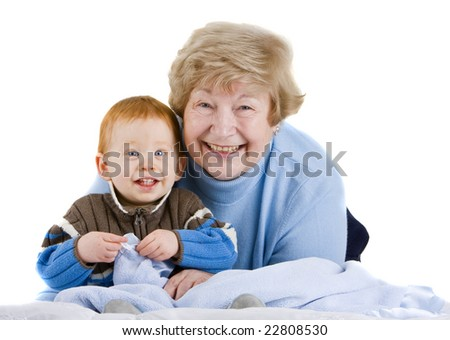 Happy grandmother with redheaded grandson sitting with blanket