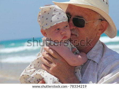 happy grandpa is holding a little granddaughter. Background - the sea.
