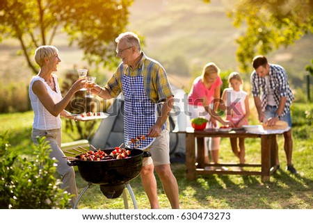 happy grandparents drink wine at barbecue