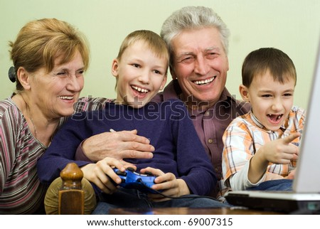 happy grandparents with their grandchildren play on the computer