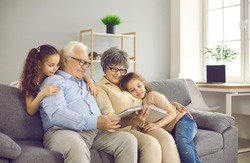 Happy grandparents with twin grandchildren browse family photo album and share happy memories. Family having fun at home sitting on sofa in living room. Concept of family history and memories.