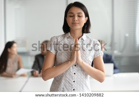 Happy grateful asian business woman meditating praying with hope standing in office with eyes closed put hands together in prayer, mindful religious chinese employee make wish feeling gratitude