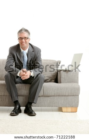 Happy gray haired businessman sitting on couch, looking at camera, smiling. Isolated on white background.?