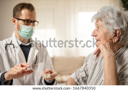 Happy gray-haired senior Caucasian woman listening as her doctor is explaining therapy details and medication dosage during house call medical check-up