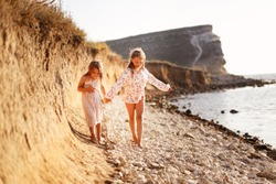 happy grimy free children run and play on a rock by the sea at sunset. Concept authentic lifestyle on vacation on a wild beach.