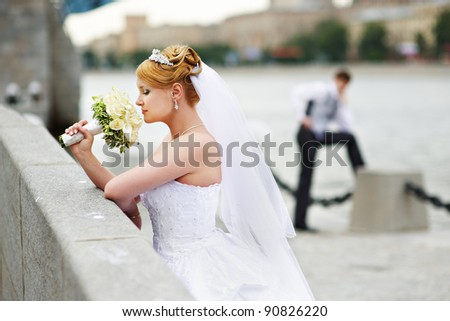 Happy groom and bride for walk on embankment of Moscow River