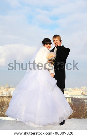 happy groom and bride with bouquet of roses embrace and look at camera at winter outdoors; man talking on phone - stock photo