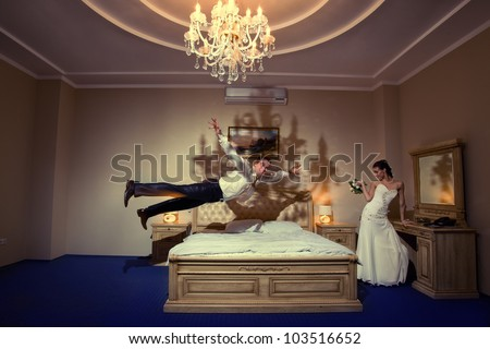 Happy groom flying on bed to his sweetheart in a stylish bed