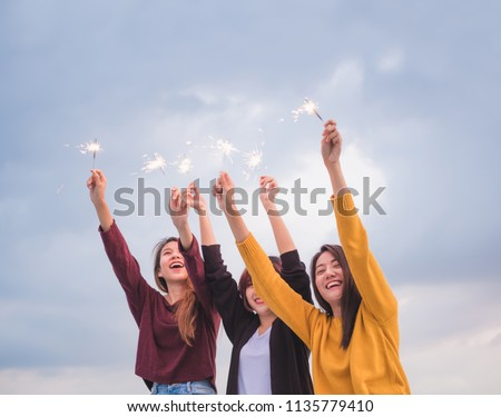 Happy group of asian girl friends enjoy and play sparkler at roof top party at evening sunset,Holiday celebration festive,teeage lifestyle,freedom and fun