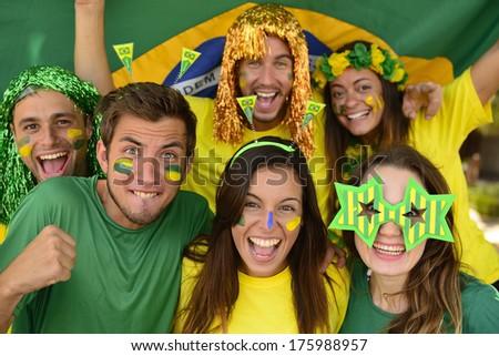 Happy group of Brazilian sport soccer fans amazed celebrating victory together. - stock photo