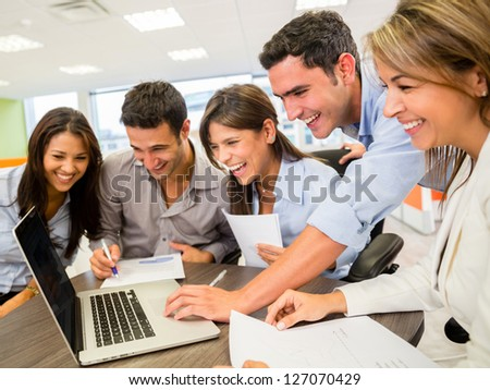 Happy group of business people looking at the computer