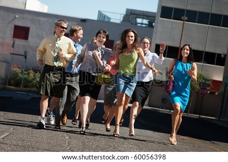 Happy group of business people running on city street
