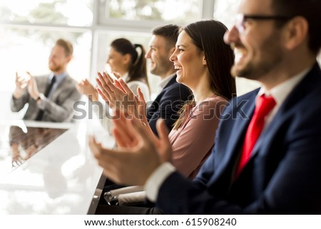 Happy group of businesspeople clapping in office