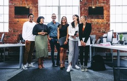 Happy group of businesspeople laughing cheerfully in a modern workplace. Diverse group of colleagues enjoying working together in an office. Successful businesspeople standing together.