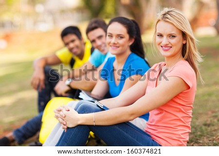 happy group of college friends sitting outdoors on campus - stock photo