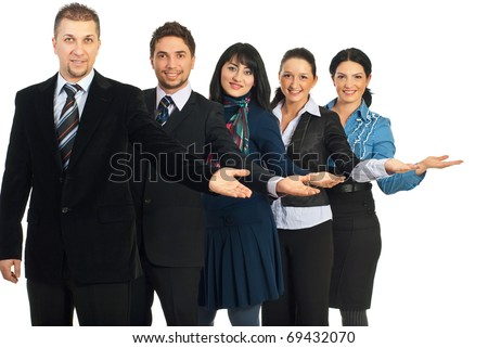 Happy group of five business people standing with open palms to copy space and welcoming isolated on white background