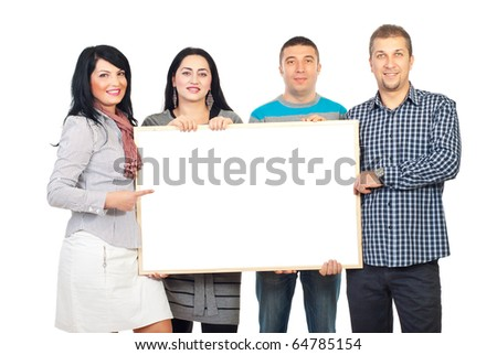 Happy group of four people holding a blank banner and one woman pointing to copy space isolated on white background