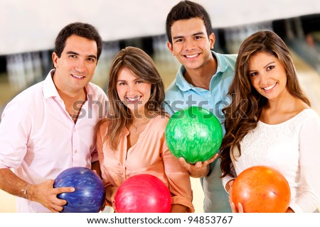 Happy group of friends bowling and holding balls