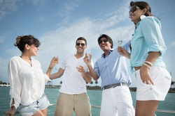 Happy group of friends drinking champagne on a yacht