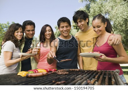 Happy group of friends gathered around grill at picnic